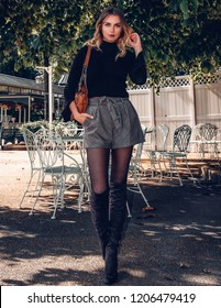 Smiling happy beautiful blonde young woman wearing a stylish fashionable stylish outfit, sweater shirt, plaid shorts skirt, tights, and boots walking on the city street park. Fall Fashion Lookbook