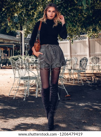 ea0393efb8a5d Smiling happy beautiful blonde young woman wearing a stylish fashionable  stylish outfit, sweater shirt, plaid shorts skirt, tights, and boots  walking on the ...