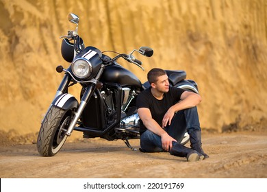 Smiling happy biker in sitting unknown on big chopper bike on road