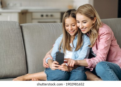 Smiling happy blonde mom and daughter dressed in stylish casual clothes, relaxing at home, using the phone, browsing the Internet, social networks, taking a selfie