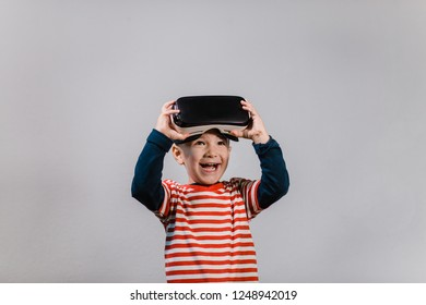 Smiling happy boy enjoying virtual reality with VR glasses. Portrait of cheerful child wearing virtual reality headset against grey background.