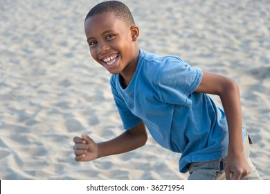 smiling happy boy has fun running at the beach, playing in sand