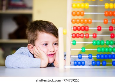 Smiling happy boy learning to count playing with abacus. Home prechool early education