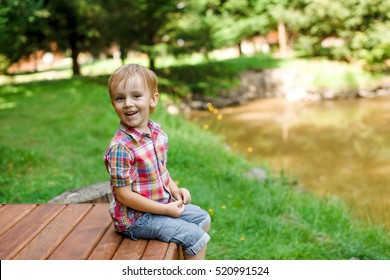 Smiling happy boy sitting on the bench near lake. Summer time weekend mood.
