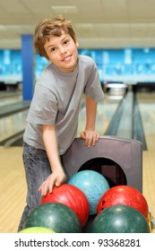smiling happy boy stands near many colorful balls in bowling club