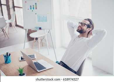 Smiling happy businessman in glasses and white shirt relaxing in office after hard working day