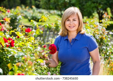 Smiling happy charming blond mature woman gardening red roses and holding horticultural tools on sunny day