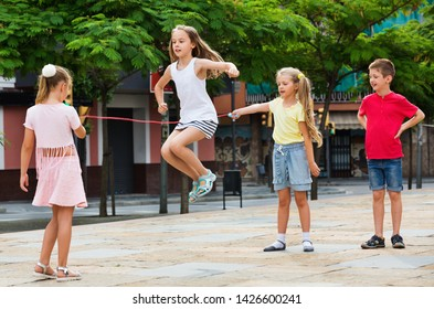 Smiling happy cheerful kids in school age playing together with jumping rope outdoors