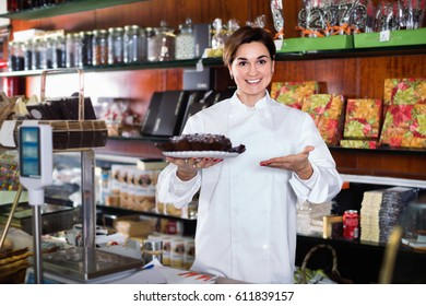 Smiling happy cheerful positive woman seller showing warm festive chocolate cake in confectionery