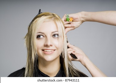 Smiling happy client while hairdresser cutting hair
