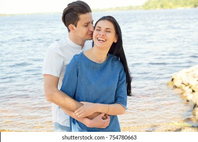 Smiling happy couple on sea. Couple in love, enjoying the summer time by the sea. Embrace the couple in love with the background of the river / sea.