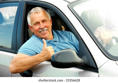 Smiling happy elderly man  in the new car