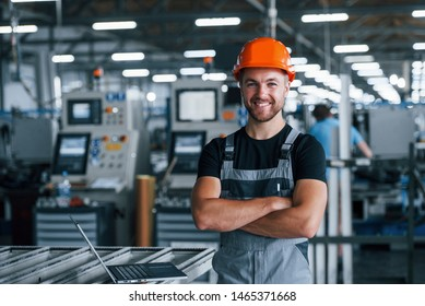 Smiling and happy employee. Industrial worker indoors in factory. Young technician with orange hard hat.