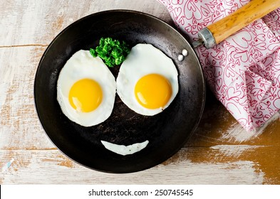 Smiling  Happy Face Frying Eggs breakfast with parsley in iron vintage pot on wooden table. Selective focus
