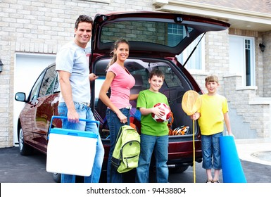 Smiling happy family and a family car.
