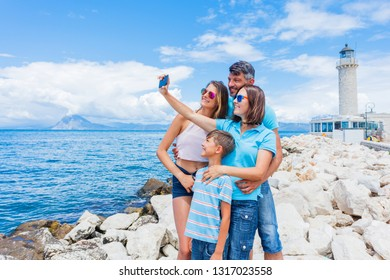 A smiling happy family of four making selfie in front of Patras lighthouse, Peloponnese, Greece. The lighthouse located on the seafront near Saint Andrew's Cathedral, is the symbol of Patras Town.