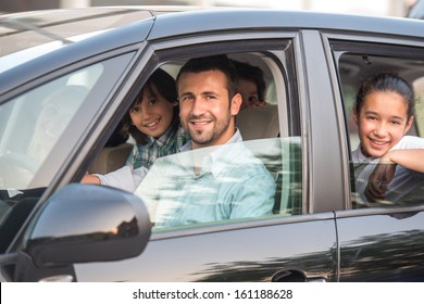 Smiling happy family sitting in car