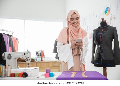 smiling happy fashion designer using mobile phone in her office
