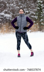 Smiling, happy fit, sporty woman on nature trail during winter. Wellness workout and healthy lifestyle concept.