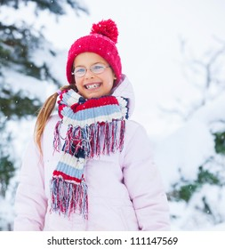 Smiling happy girl having fun outdoors on snowing winter day in Alps playing in snow.