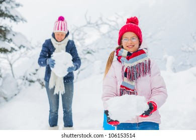 Smiling happy girl with her mother having fun outdoors on snowing winter day in Alps playing in snow.