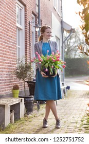 smiling happy girl holding a vase with pink tulips near with a traditional Dutch house. The Netherlands