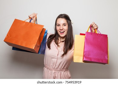 Smiling happy girl with lots of products in bags