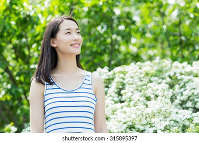 smiling happy girl in the park, asian woman