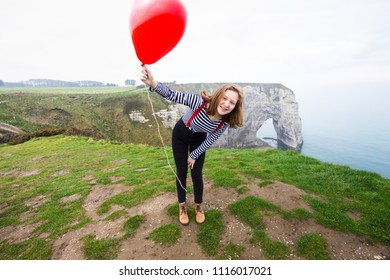 smiling happy girl with a red balloon in the shape of a heart at background of scenery Etretat. France