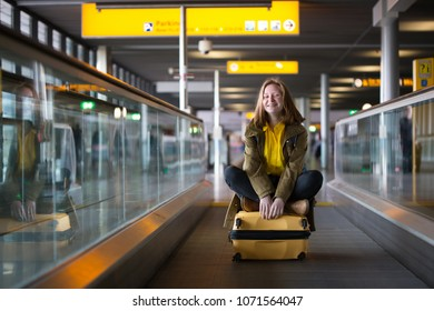 the smiling happy girl is riding on the travolator at the airport with a large yellow suitcase