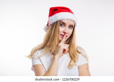 smiling happy girl says shh secret and puts finger on lips on white background
