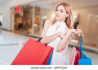 Smiling happy girl with shopping bags walking in the mall and buying gifts