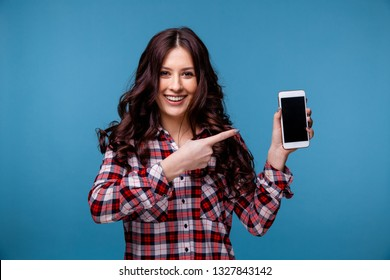 Smiling happy girl showing new phone isolated.