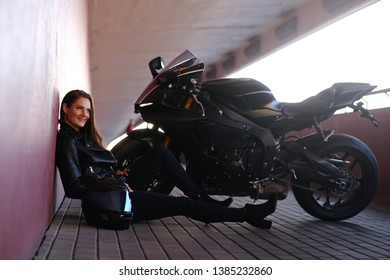 Smiling happy girl is sitting in tunnel near her motobike and helmet. She is wearing leather jacket and heels.