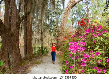 Smiling happy girl walking in beautiful garden on spring trip. Young woman relaxing in the park. Azaleas in bloom under oak tree. Magnolia Plantation and Gardens, Charleston, South Carolina, USA