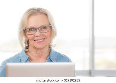 A smiling happy good looking blonde woman looks directly at camera while at her laptop