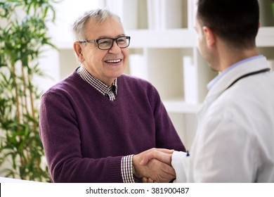 Smiling happy healthy old male shaking with doctor in office