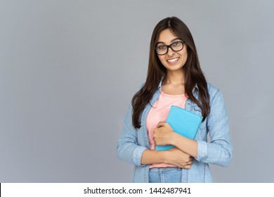Smiling happy indian young woman college university school student wear glasses holding book isolated on grey studio background, positive teen girl looking at camera stand with copy space, portrait