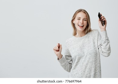 Smiling happy joyful girl dances, holds mobile phone, being glad to recieve message from boyfriend, listens to pleasant melody in white earphones, isolated against wall with copy space