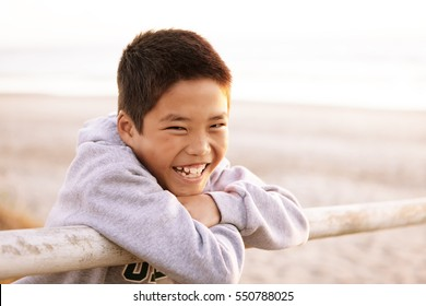 Smiling, happy Korean boy hanging over a fence on the Oregon coast.
