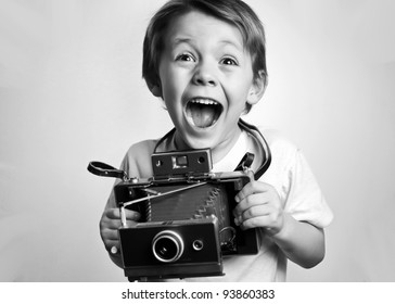 smiling ,happy, laughing,boy,young child ,photographer holding a (Polaroid type) instant camera on a white background