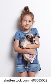 Smiling happy little girl is holding a puppy in her hands on a white background.