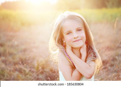 Smiling, happy little girl on a sunny summer meadow field