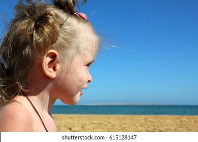 smiling happy little girl on beach near sea
