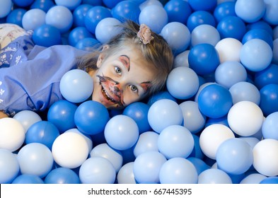 A smiling happy little girl playing in the balls pool. Family weekend concept.