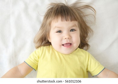 smiling happy little girl portrait expressive positive emotional face lying on bed isolated, happy childhood concept
