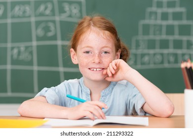 Smiling happy little schoolgirl in class sitting at her desk n front of the blackboard grinning at the camera