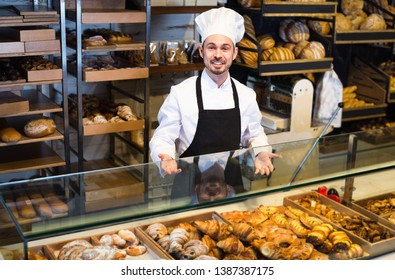 Smiling happy  man baker showing warm tasty croissant in bakery