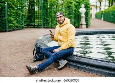 Smiling happy man with bristle wearing casual clothes and big eyewear sitting crossed legs near fountain in park holding cell phone messaging with his girlfriend having delightful expression