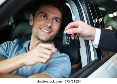 Smiling happy man sitting in his new car and taking keys from a dealers hand at the salon